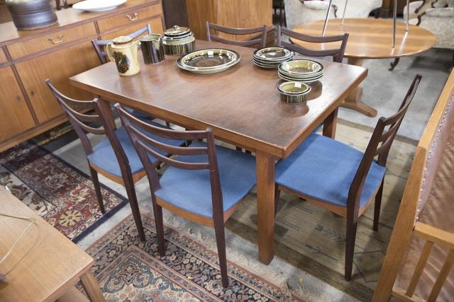 Ruskea pöytä ja sinisellä kankaalla verhoillut tuolit